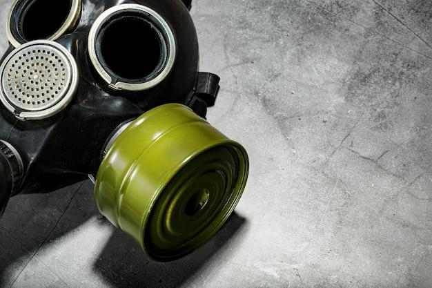 Gasmaske auf einem schwarzen steinhintergrund, schutz vor gefährlicher infektion. Premium Fotos