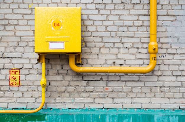 Gasversorgungsrohre mit armaturenbrett gegen backsteinmauer Premium Fotos