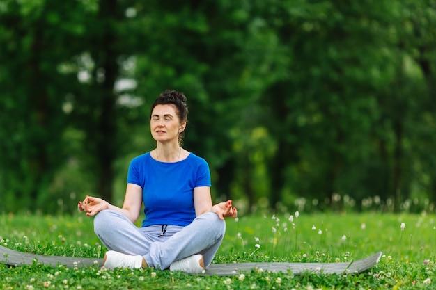 Gealterte frau, die yogaübung im park tut. übendes outdor yoga der älteren frau Premium Fotos