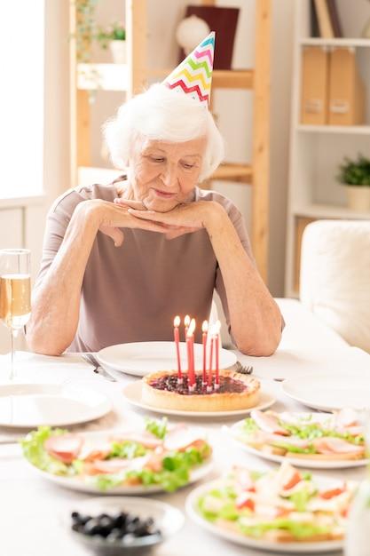 Gealterte frau im ruhestand, die brennende kerzen auf hausgemachtem kuchen beim sitzen am servierten geburtstagstisch betrachtet Premium Fotos