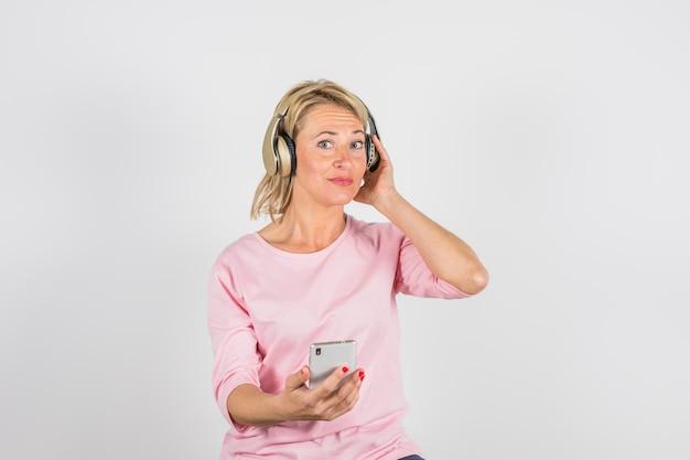 Gealterte frau in der rosafarbenen bluse mit kopfhörern unter verwendung des smartphone Kostenlose Fotos