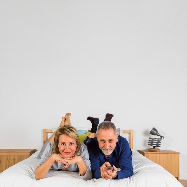 Gealterte Glückliche Frau Und Mann Mit Fernsehfernbedienung Auf Bett