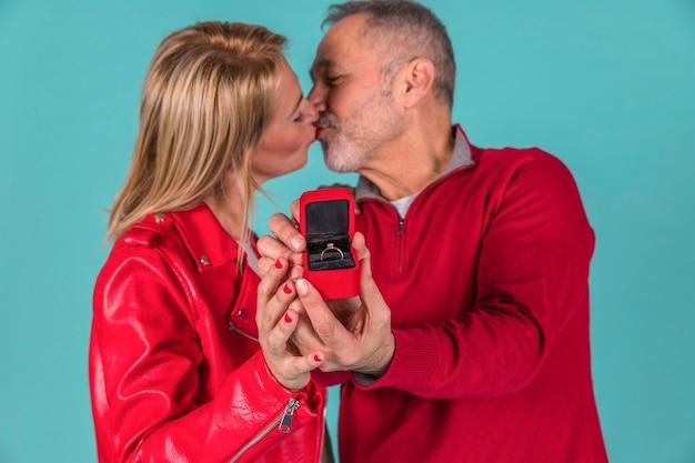 Gealterter mann, der mit frau küsst und schmuckkasten zeigt Kostenlose Fotos