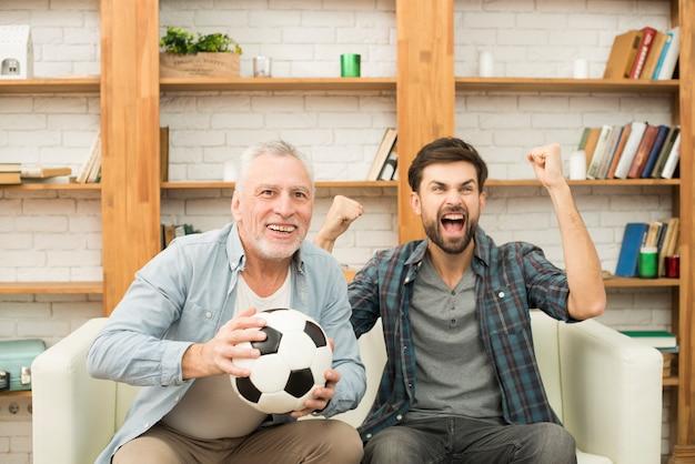 Gealterter mann mit dem ball und jungem schreiendem kerl, die auf sofa fernsehen Kostenlose Fotos