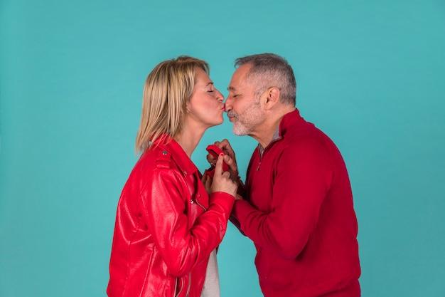 Gealterter mann mit dem schmuckkasten, der mit frau küsst Kostenlose Fotos