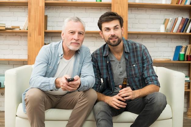 Gealterter mann mit fernbedienung und junger kerl mit flasche auf sofa fernsehend Kostenlose Fotos