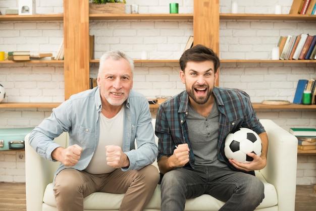 Gealterter mann und junger schreiender kerl mit ball auf sofa fernsehend Kostenlose Fotos