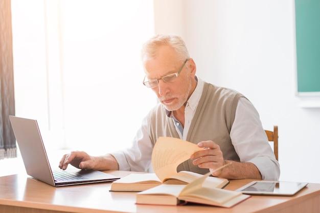 Gealterter professormann, der mit laptop beim lesebuch im klassenzimmer arbeitet Kostenlose Fotos