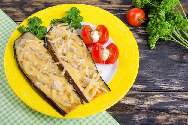 Gebackene auberginen mit parmesan, sonnenblumenkernen und tomaten Premium Fotos