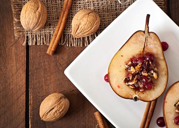 Gebackene birnen mit preiselbeeren, honig und walnüssen Premium Fotos
