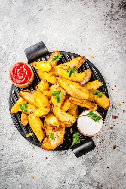 Gebackene bratkartoffeln mit den roten und weißen soßen der knoblauchkräuter auf grauem steinhintergrund Premium Fotos
