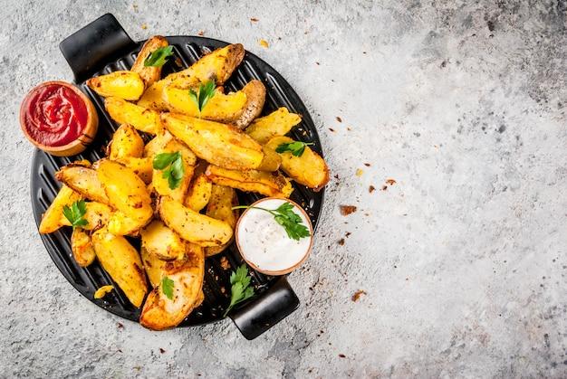 Gebackene bratkartoffeln mit knoblauch, kräutern, roten und weißen soßen Premium Fotos