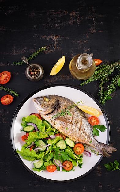 Gebackene fischdorado mit zitrone und frischem salat in weißer platte Kostenlose Fotos