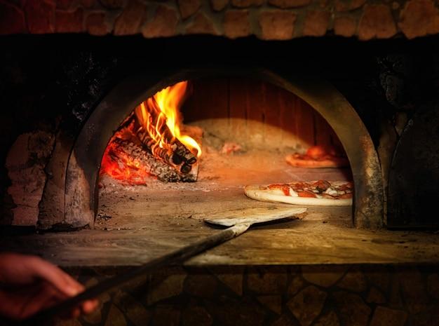 Gebackene geschmackvolle margheritapizza, die den ofen verlässt Premium Fotos