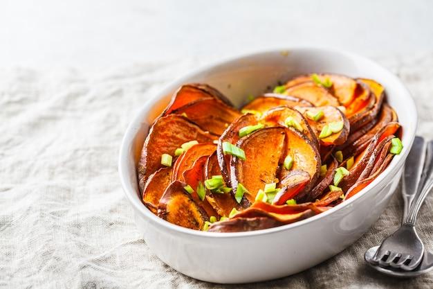 Gebackene geschnittene süßkartoffel mit frühlingszwiebeln im weißen teller. Premium Fotos