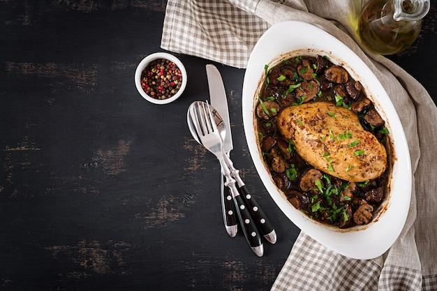 Gebackene hühnerbrust mit pilzen in der balsamico-sauce auf dem tisch. ansicht von oben Premium Fotos