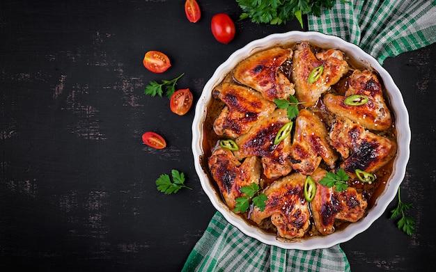 Gebackene hühnerflügel im asiatischen stil auf auflaufform. draufsicht über kopf Premium Fotos