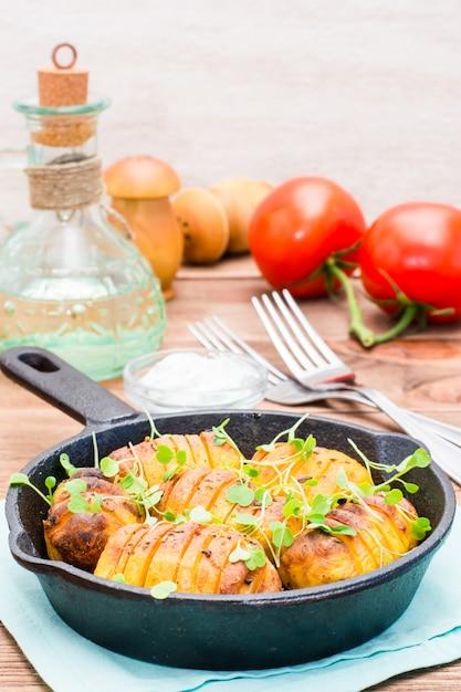 Gebackene junge kartoffeln in den gewürzen und im öl mit arugula in einer eisenwanne auf einem holztisch Premium Fotos