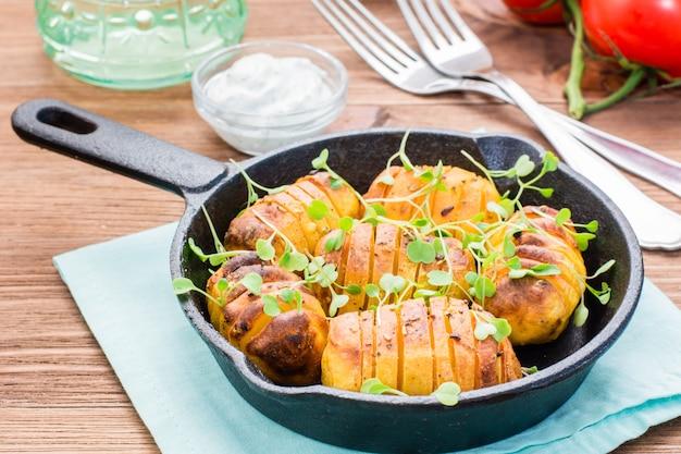 Gebackene junge kartoffeln in den gewürzen und im öl mit arugula in einer eisenwanne und in einem sauerrahm auf einem holztisch Premium Fotos