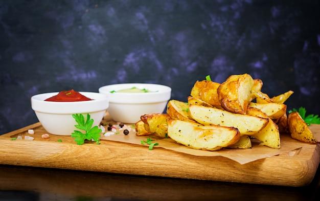 Gebackene kartoffeln mit sauce und gewürzen auf dunklem Premium Fotos