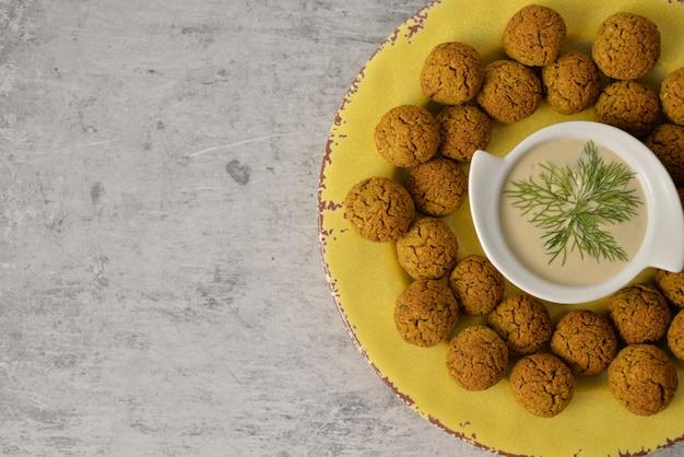 Gebackene kichererbsenfalafelbälle auf gelber platte auf grauem, gesundem und veganem lebensmittel mit tiefem, traditionellem mittelmeer, draufsicht, ebenenlage mit kopienraum Premium Fotos