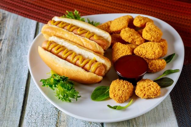 Gebackene knusprige hühnernuggets und hot dogs auf weißem teller. Premium Fotos