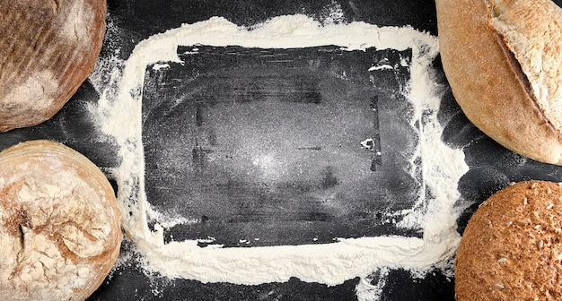 Gebackene verschiedene brotlaibe auf einem schwarzen hintergrund Premium Fotos