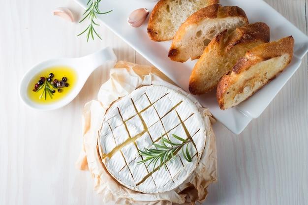 Gebackener camembert- oder briekäse auf einem hölzernen brett. Premium Fotos