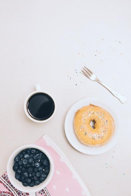 Gebackener donut; kaffeetasse; serviette; gabel und blaubeeren auf weißem hintergrund Kostenlose Fotos