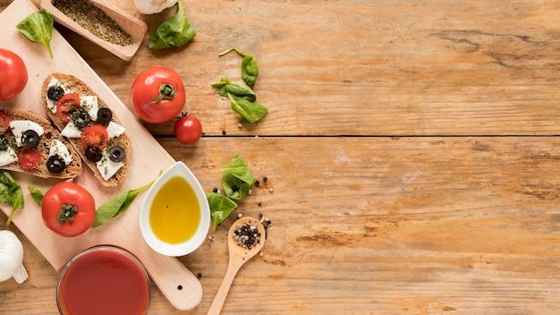 Gebackenes brot mit belag und gemüse auf schneidebrett Kostenlose Fotos