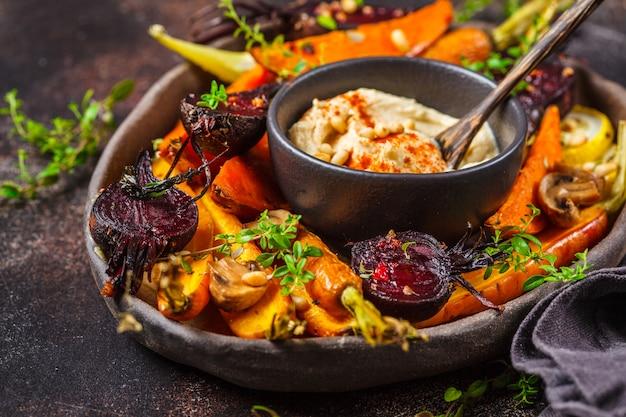 Gebackenes gemüse mit hummus in einem dunklen teller. Premium Fotos