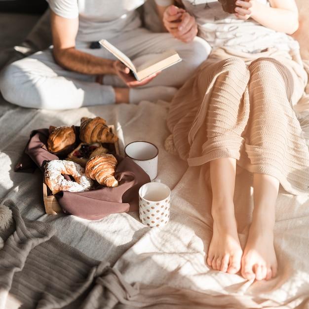 Gebackenes hörnchen und tasse kaffee mit den paaren, die auf bett sitzen Kostenlose Fotos