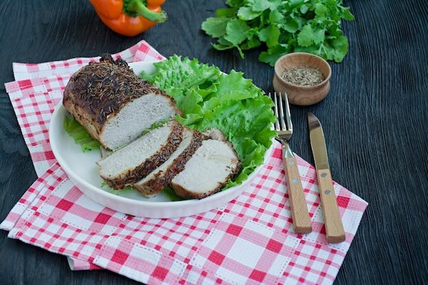 Gebackenes schweinefilet in den gewürzen geschnitten auf einer weißen platte mit grünem salat. Premium Fotos