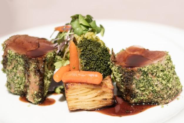 Gebackenes schweinefilet in kräuterkruste mit kartoffeln, karotten, brokkoli, sauce und kräutern Premium Fotos
