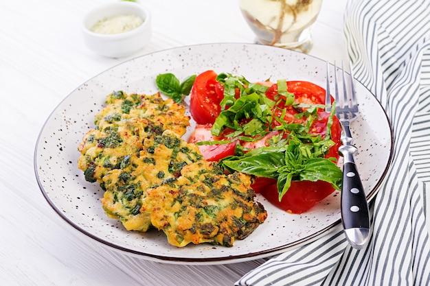 Gebackenes steak gehacktes hähnchenfilet mit spinat und einer beilage tomatensalat. europäische küche. diätetisches essen. Kostenlose Fotos