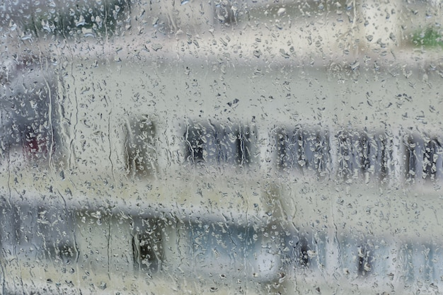 Gebäude auf dem hintergrund eines nassen fensters mit regenstreifen. Premium Fotos
