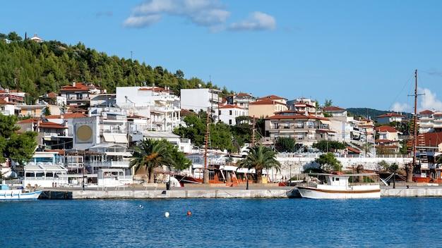 Gebäude auf einem hügel mit viel grün, pier mit festgemachten booten im vordergrund, neos marmaras, griechenland Kostenlose Fotos