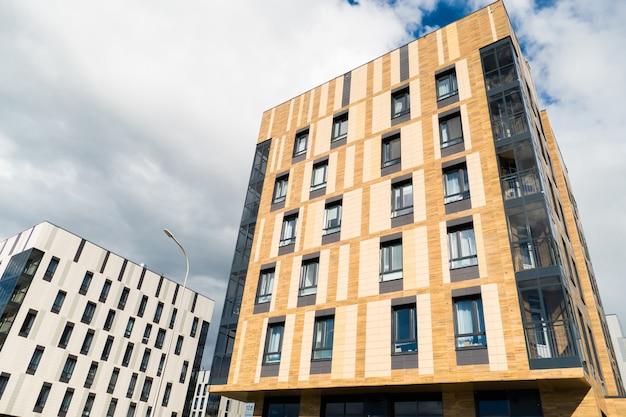 Gebäude in weißer und brauner farbe in zeitgenössischem stil. das untere gras und die bäume. Premium Fotos