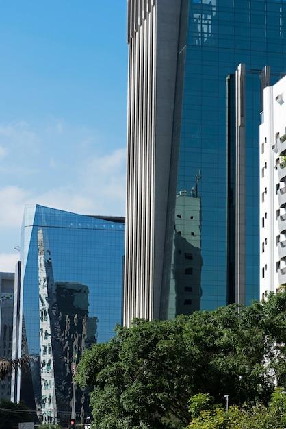 Gebäude mit der glasfassade, welche die straße reflektiert Premium Fotos