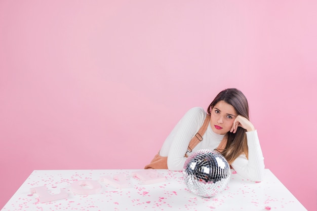 Gebohrte frau, die am tisch mit discokugel sitzt Kostenlose Fotos
