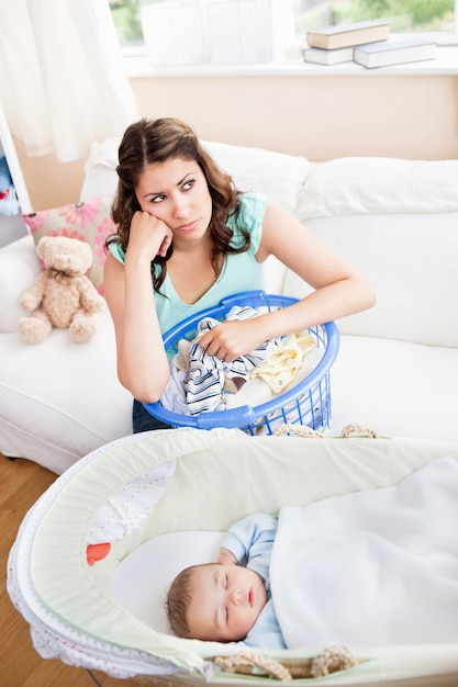 Gebohrte mutter, die auf ihr baby wartet, um im sofa mit ihrem wäschekorb zu sitzen aufzuwachen Premium Fotos