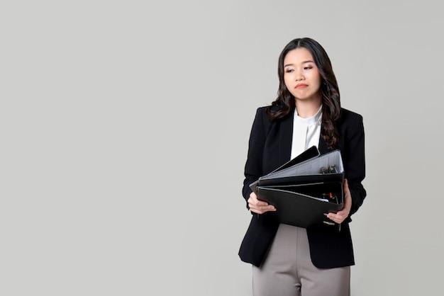 Gebohrte unglückliche asiatische geschäftsfrau, die dokumentdateien verwahrt Premium Fotos