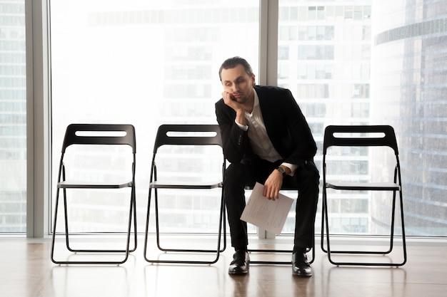 Gebohrter junger mann in der klage, die im warteraum sitzt. Kostenlose Fotos