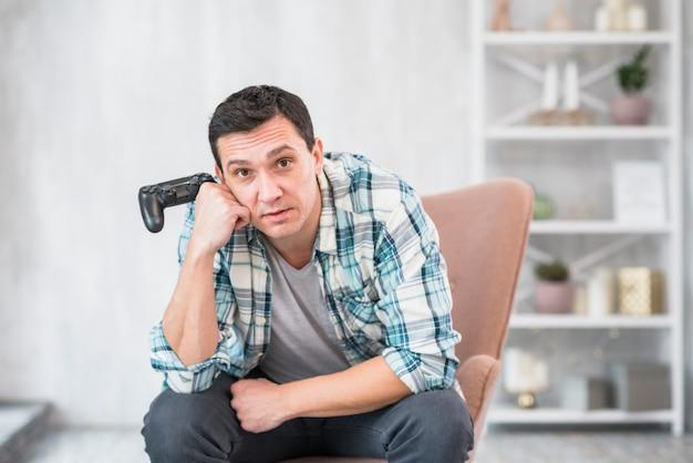 Gebohrter kerl, der im lehnsessel mit gamepad sitzt Kostenlose Fotos