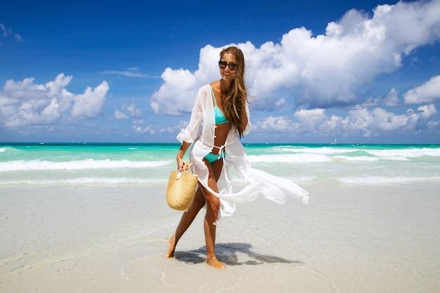 Gebräuntes mädchen im blauen bikini und in weißem tunika, die auf der küste stehen. Premium Fotos