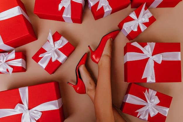 Gebräuntes mädchen in den roten schuhen, die nach neujahrsparty aufwerfen. glamouröses weibliches modell, das auf dem boden mit geschenken sitzt. Kostenlose Fotos