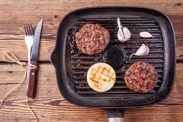 Gebratene burger-beef-schnitzel mit zwiebeln und knoblauch auf grillpfanne mit gabel und messer Premium Fotos