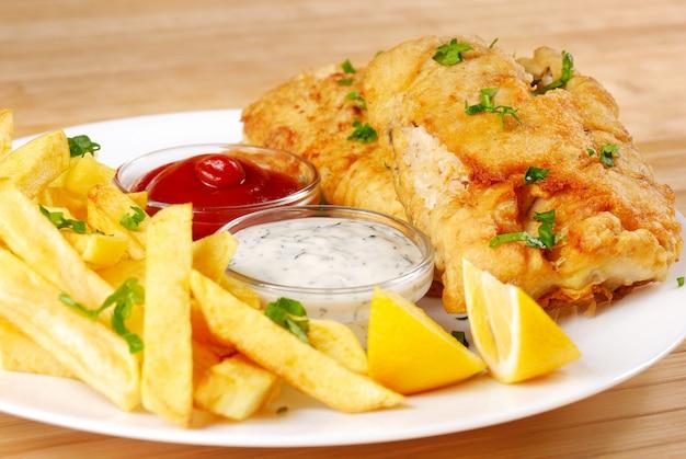 Gebratene fish and chips auf weißem teller Premium Fotos