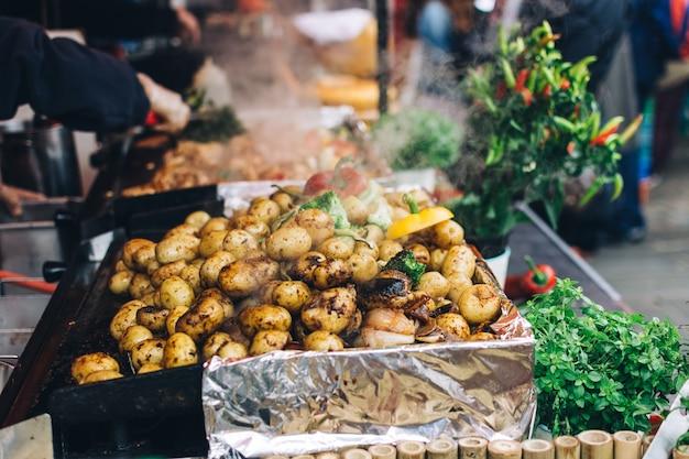 Gebratene ganze kartoffeln mit gemüse auf einem lebensmittelmarkt Kostenlose Fotos