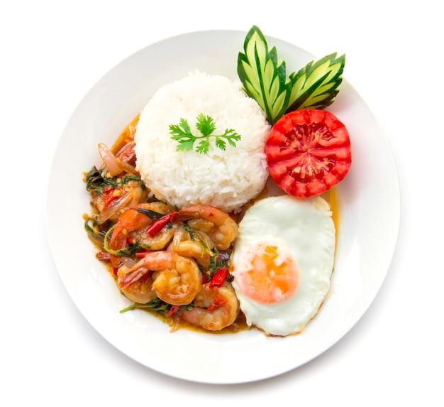 Gebratene garnele des thailändischen lebensmittels würzig und basilikum diente mit reis und spiegelei und tomatengurke Premium Fotos